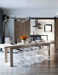 Dining room with clear lucite chairs, a long, thin, reclaimed wood farmhouse style dining table