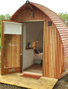 The curved walls/roof make this small cabin look like an upturned section of a ship's hull.