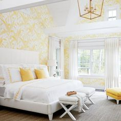 White and yellow bedroom features a vaulted ceiling accented with a Darlana Medium Lantern illuminating walls clad in Meg Braff Meadow Reed Wallpaper lined with a white bed with tall headboard dressed in white and yellow bedding as well as yellow pillows alongside a pair of white x stools placed at the foot of the bed.