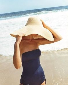 Beach wear: Navy swimsuit and straw hat.