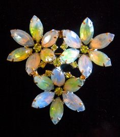A KRAMER of NEW YORK blue-green opalescent brooch with peridot rhinestones in a flower motif....vintage:  An exquisite brooch by Kramer of New York in a 3-flower motif. The givre rhinestones are amazing with a blending of green and blue colors and an occasional flicker of soft orange. Peridot rhinestones are nestled in the flowers center...everything is prong set. The back is silver plated, and the flowers are raised or angled to give it a dimensional effect.  Size .... 2-1/4 x 2-1/4…