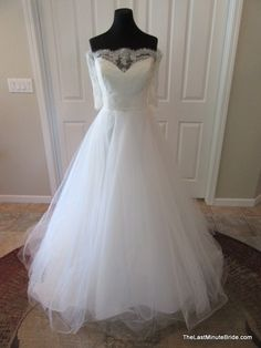 Description Alencon lace off the shoulder wedding dress with a sweetheart illusion neckline and a full tulle ball gown skirt. The dress features three quarter length alencon lace sleeves. The back of