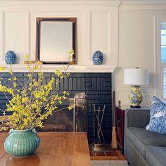 Trim Design Co. | Black painted brick for your fireplace surround creates a crisp, classic & sophisticated focal point in any living room or family room. It is unexpected and instantly adds drama. Keep things light and airy by painting the woodwork a warm white, using a mirror on the mantel to reflect and bounce light around the room, and add cheerful color and pattern with accessories like pillows, lamps, vessels & plants/flowers.   #trimdesignco #fireplaceideas #blackfireplace #blackbrick