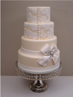 white/cream over pale apricot a stunning cake completed with ribbon and brooche