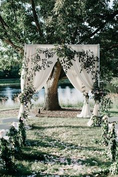 Whimsical wedding decor idea - outdoor ceremony arch - white fabric with greenery {LOLA Event Productions}
