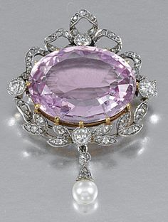 PINK TOPAZ AND DIAMOND BROOCH/PENDANT, CIRCA 1905.  Set to the centre with an oval pink topaz within a stylised foliate frame set with circular- and rose-cut diamonds to a cultured pearl drop, to a later detachable drop.