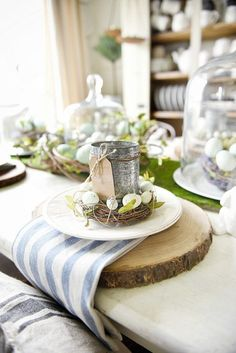 Easter Table - Easter Tablescape with moss, eggs, nests, tin cans and name cards. Inspiring Farmhouse Easter Decor. Creative Spring Fixer Upper Ideas including rustic metals, moss, bunnies, eggs and distressed woods. #farmhouse #easter #easterdecor #homedecor #farmhouesdecor #spring #springdecor #hometour #farmhousestyle #fixerupper #joannagaines #springhometour #potterybarn #napkins #table #tablescapes