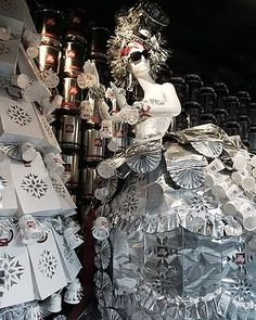 Barneys New York  Here we meet Ms. Illy, the centerpiece of Doonan's windows. Ms. Illy is fashioned from recycled Illy espresso tins and foil. Doonan and his team used 300 three-kilo Illy tins, 250 foil bags, and 250 8.8-oz. Illy cans to create her. Ms. Illy has an espresso machine headpiece (Illy's Francis X1 iperEspresso machine), a coffee-scoop earring, and a festive holiday garland made from 300 paper cups.