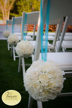Pomander balls of white carnations will hang off the pews at the ceremony site from ribbon...but in pink