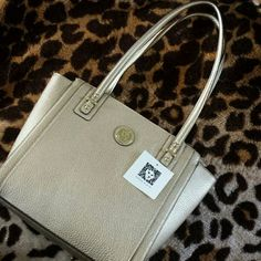 SALE! Anne Klein classic gold purse Never used. Purse has small pocket in the back. The inside is polka dot black and white. There's a zipper pocket on left side and two open pockets on right side. Anne Klein Bags