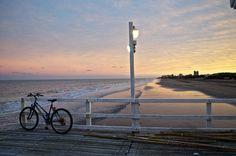 Paisaje de un atardecer desde el Muelle de La Lucila del Mar. Una bicicleta y las primeras luces de la noche sobre la playa y el mar.