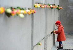 BERLÍN, ALEMANIA, 9 DE NOVIEMBRE: Una niña desliza una rosa en un segmento conservado del Muro de Berlín durante las conmemoraciones con motivo del aniversario número 25 de la caída del muro, en el Memorial del Muro de Berlín, en Berlín, el 9 de noviembre del 2014.