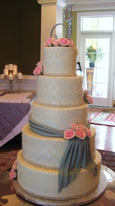 Five tier round buttercream wedding cake with gray fondant sash and pink sugar roses. Decorated with diamond impression, small scrollwork, and rhinestone/pearl banding.