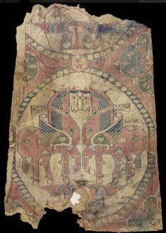 Sogdiana, Central Asia, circa 8th Century. Woven in red, blue, green and cream silks with a large scale pearl roundel, enclosing two confronted winged horses standing on a winged split palmette, standing with front legs raised, the bodies with geometric and heart-shaped motifs, pearl bands around their necks, joined to a part roundel above by a rosette plaque, the interstices with stylised lotus flowers, attached to a golden colour silk textile with lozenge design, mounted, 65 x 39.4 cm…