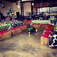 John Deere birthday setting using hay bales, cow print, and plenty of green. See more John Deere birthday party ideas at www.one-stop-party-ideas.com