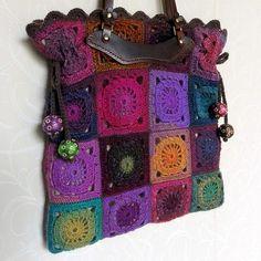 Flower-power crochet handbag with leather handles, and pom poms. So boho.