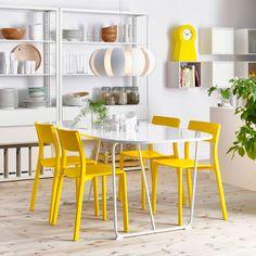 Salle à manger avec une table ovale blanche et des chaises jaunes. En association avec une étagère blanche garnie de verres, assiettes et bols.