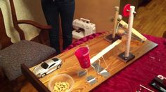 A Rube Goldberg machine is an extremely complex apparatus that performs a very simple, very easy task in an indirect and convoluted way. Description from hmongreplay.com. I searched for this on bing.com/images