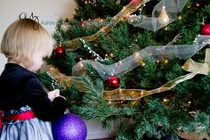 Baby Girl Trimming the Tree Christmas Time