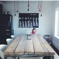 Multiple hanging Edison bulbs on fabric wrapped cords, black Smeg, large black wall calendar, plank and pipe table