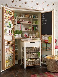 """Wenn es seine Größe zulässt kann der Hauswirtschaftsraum selbstverständlich auch als Vorratskammer genutz werden. Neben Gewürzen, Essig und Zwiebeln oder Kartoffeln lassen sich in diesem Schrank (Model """"Dorset White Pantry"""" von Laura Ashley, 2015) auch jede Menge Kochbücher und ein ausziehbarer Servierwagen mit Arbeitsfläche Platz."""