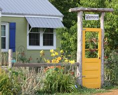 Yellow Garden Gate (Oh, look at this! It's a happy garden gate made from an old door painted yellow. This is one of the best ideas I've seen for a DIY garden gate. You can make this!)