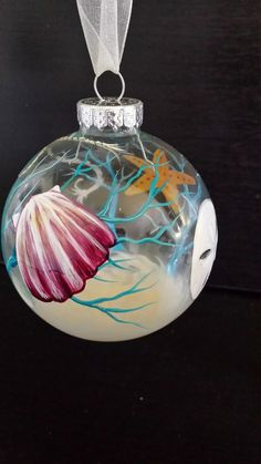 Beach Ornament Nautical Holiday Decor Hand Painted Glass Starfish Seashell Sand Anchor Coral Sandollar Sea Ocean Florida Coastal Unique Gift Looking for a unique ornament that will take your nautical theme tree over the top this year for Christmas? Have a friend who lives at the beach? This beautifully hand painted glass ornament is just what you need to bring on the sea! The imagery includes a highly detailed seashell, sand dollar, anchor and star fish surrounded by bright blue coral. At…