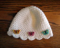 Delicate white crochet baby beanie with colorful butterflies. Perfect for the little girl in your life! Comes with a matching pair of booties! #baby #babygirl #babyshower #booties #beanie #hat #scalloped #butterflies #colorful #DIY #crochet #knit #gift #abitofshabbychic