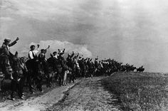 by David Seymour - SPAIN. Extremadura. A committee of peasants saluting, with their fists, militians leaving to join the forces in Madrid. 1936 // Magnum Photos