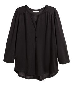 Wide-cut top in soft, airy jersey. V-neck and buttons at front, 3/4-length puff sleeves, seam at yoke, and rounded hem with short slits at sides.