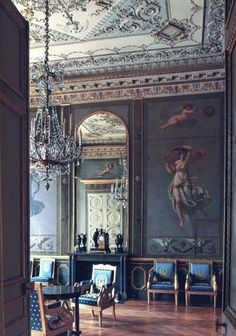 An 18th century Rococo interior featuring Fauteuil chairs with padded armrests. Beautiful imagery covering the expansive wall and ceiling. Gold gilt trim detail consistent with the era brings a sense of wealth and grandeur to the space.