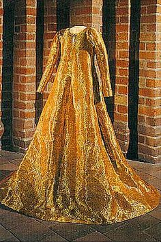Possibly the burial gown of Queen Margaret of Denmark, who died in 1412. The fabric was really splendid, a mixture of gold and silk.  The pattern consisted of 4 pattern-pieces, but every pattern-piece was sewn together from many smaller pieces of fabric, to make a more economic use of it. Sleeves were almost not preserved, but their remains indicate that the were probably long, up to the wrists, and narrow all the way.