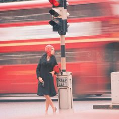 Woman. Traffic. London. Full of red. In 1960. Through the lens of Norman Parkinson.