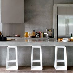 intriguing concrete kitchen with modern white stools