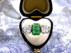 Art Deco Emerald Ring dating from circa 1940 featuring a Rich Green Colombian Emerald flanked by two Fiery White Diamonds set in an ornate 18ct Yellow Gold & Platinum.