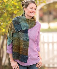 The woven-plaid look of this rectangular wrap is achieved with a simple seedstitch pattern combined with vertical intarsia columns and horizontal stripes to create a subtle interplay of colors. The wrap begins with blocks of single-color ribbed-cable cast-on and ends with