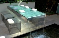 Glass table with running water, looks cool but probably makes you pee more often when you are having dinner with friends.