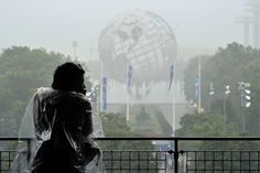 Fans trying to stay dry during a rain delay prior to the Men's Singles Semifinals match on Day 13 of the 2012 US Open. - Getty Images