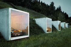 """Le"""" parking nature"""" de l'architecte Peter Kunz est situé à Herdern en Suisse. Le garage est enfoui dans la terre avec des ouvertures carrées et un vitrage laissant apparaître le véhicule en stationnement."""