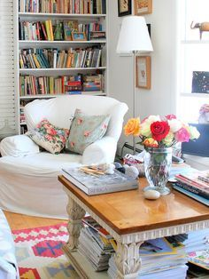 This cozy reading nook is full of brightness, both from the natural light and the colors on the pillows and bookshelf!