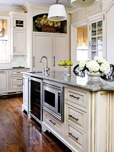 Traditional French Kitchen: Island Arrangement  Small appliances, including a wine fridge and microwave, tuck into the island on the working side of the kitchen. The large run of uninterrupted countertop is perfect for prepping and serving large meals.
