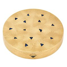 18k Gold and Sapphire Compact, Cartier Circular gold compact applied with an engraved stylized star design, accented by 15 triangular-shaped sapphires, with mirror.
