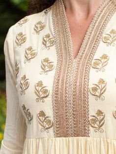 Our stunning Maharana Dress in soft buttery yellow is simply regal.  Yards of fabric set in tiers give this statement dress wonderful movement.   Gold, floral embroidery sits on both sides of a gold braided placket that also surrounds the neckline. Truly a magnificent tribute to the luxurious sophistication of Indian design. Attached gold lurex bands on the sleeves and hemline.