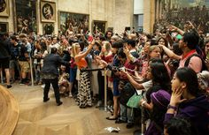 """A crowd viewing the """"Mona Lisa"""" at the Louvre in Paris, the busiest art museum in the world."""