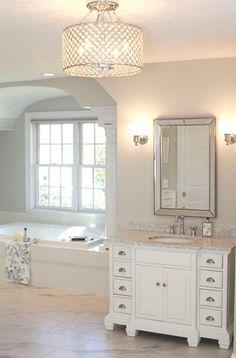 Paint Color: Benjamin Moore OC-56 Moonshine. Chandelier: Chrome & Crystal 4-light Round Ceiling Chandelier ($132.99), Overstock.com Vanities (Allen+Roth) and Sconces: Lowe's Flooring: Ceramic Tile from Tile America