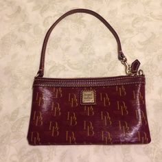 Dooney and Bourke Large wristlet DB large wristlet from their 1975 collection I bought at Macy's a few years ago. Maroon with red interior. Excellent used condition. Only carried a handful of times. Raising $ for my medical bills. Dooney & Bourke Bags Clutches & Wristlets