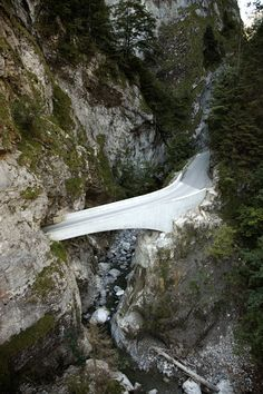 Arching concrete bridge designed for a winding mountain road between two Alpine towns.