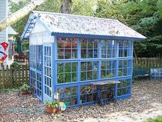 greenhouse made of old windows. Old window greenhouse, using recycled windows from one neighbor who was replacing all the windows on her house, and a couple of old doors from another neighbor who was getting new ones installed.