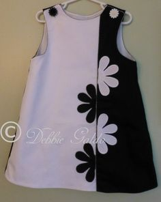 By Debbie Galdo. Black & white cotton pique A-line (Lucy pattern by Children's Corner), colorblocked & piped with black & white gingham. Flowers, with french knot centers, are appliqued to either side of piping.