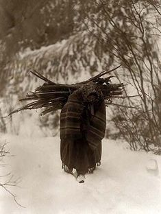 Heavy Load. It was made in 1908 by Edward S. Curtis.    The illustration documents a Dakota Sioux woman carrying firewood on her back in snow.